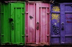 Verde, rosa y envases púrpuras en el ambiente urbano imagen de archivo libre de regalías