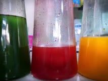 Verde, rosso e succo d'arancia in bottiglie di vetro alte Fotografia Stock