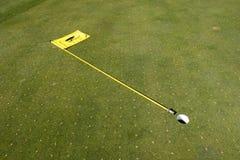 Verde ventilado do golfe com a bandeira puxada Fotografia de Stock Royalty Free
