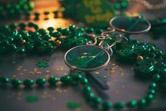 Verde: Vidros do duende no fundo do metal e dos confetes Imagens de Stock Royalty Free