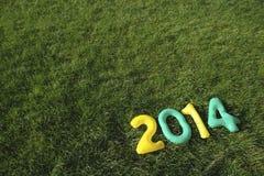 Verde y amarillee el mensaje 2014 en fondo de la hierba Imágenes de archivo libres de regalías