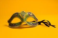 Verde y oro Mardi Gras, máscara veneciana en fondo amarillo Foto de archivo