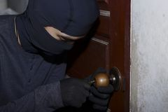 Verdeckter Dieb mit dem Kopfschutz, der in der Nacht an einem Haus teilnimmt und bricht Übergeben Sie das Anhalten einer Pistole  Stockfotografie