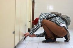 Verdeckter Dieb mit einem Kopfschutz ein Foto mit intelligentem Mobiltelefon in der Toilette schleichend und machend Stockbilder