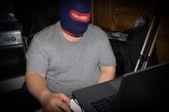 Verdeckter Terrorist, der an seinem Computer arbeitet Konzept über internat stockfotografie