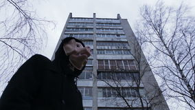 Verdecktes Mannschwein auf dem Hintergrund eines Apartmenthauses stock video