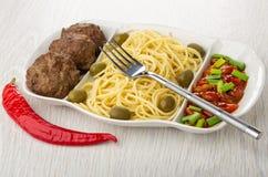 Verdeelde schotel met spaghetti, kotelet, bonen, groene ui en olijven, vork, Spaanse peperpeper op lijst stock afbeelding