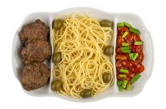 Verdeelde schotel met spaghetti, kotelet, rode bonen, ui en olijven die op wit wordt geïsoleerd Hoogste mening royalty-vrije stock fotografie