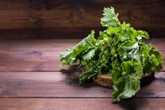 Verdes de nabo orgânicos crus prontos para comer em um fundo de madeira marrom com espaço da cópia imagem de stock