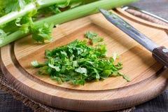 Verdes desbastados do aipo em uma placa de corte Imagem de Stock