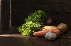 Verdes e colheitas de raiz em uma tabela rústica escura Foto de Stock Royalty Free