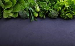 Verdes: espinafres, pepino, brócolis, alho, hortelã, salsa, alface, cebola em um fundo preto Fotos de Stock