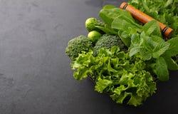 Verdes: espinafres, pepino, brócolis, alho, hortelã, salsa, alface, cebola em um fundo preto Fotografia de Stock