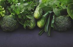Verdes: espinafres, pepino, brócolis, alho, hortelã, salsa, alface, cebola em um fundo preto Imagem de Stock