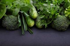 Verdes: espinafres, pepino, brócolis, alho, hortelã, salsa, alface, cebola em um fundo preto Foto de Stock