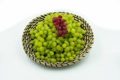 Verdi freschi ed uva rossa in un canestro Fotografia Stock