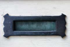 Verdigris Brass Letter Box in an Off White Door. Stock Image