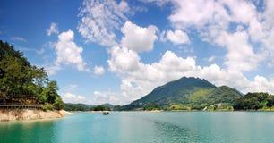 Verdissez l'eau et le ciel bleu Photographie stock libre de droits