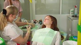 Verdovingsmiddeleninjectie in tandkabinet Vrouwelijke tandarts die injectie doen stock videobeelden