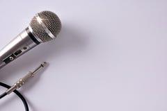 Verdrahtetes Mikrofon mit Verbindungsstück auf Draufsicht der weißen Tabellennahaufnahme Lizenzfreie Stockfotos