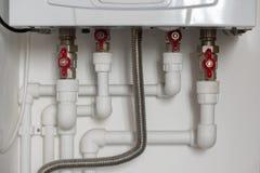 Verdrahtung von Kunststoffrohren zum Warmwasserbereiter in der Wohnung stockbilder