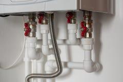 Verdrahtung von Kunststoffrohren zum Warmwasserbereiter in der Wohnung lizenzfreie stockbilder