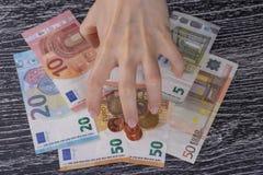 Verdreht durch Habsucht, die Hand der Frauenr?hrstangen herauf ein B?ndel Euroanmerkungen und die M?nzen zu selbst lizenzfreies stockfoto