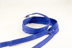 Verdrehter blauer Reißverschluss auf einem hellen Stoff stockfotografie