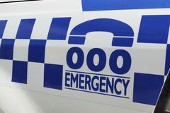 Verdreifachen Sie nullzahlen und blaues und weißes Zeichen auf einem Polizeiwagen Lizenzfreies Stockfoto