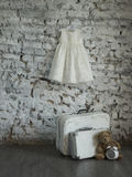 Verdress. The dress hangs on the wall. Teddy bear sitting on the floor next to the clock against a white brick wall and suitcases Royalty Free Stock Photography