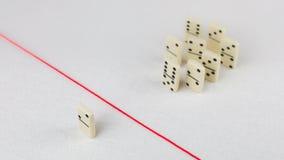 Verdreven van de groep, onbekwaam om de rode lijn te kruisen die hen scheidt Scène met groep domino Concept van Stock Afbeeldingen