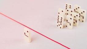 Verdreven van de groep, onbekwaam om de rode lijn te kruisen die hen scheidt Scène met groep domino Concept van Stock Foto