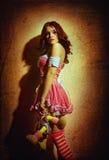 verdriet vrouw in roze kleding en weinig pop Royalty-vrije Stock Foto