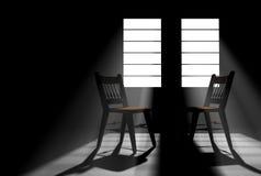 Zwei leere Stühle in einem verdunkelten Raum Stockbilder