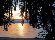 Verdunkelung des Sonnenunterganghimmels über dem See mit bunten Wolken und dunklen Schattenbildern von Bäumen, goldene Stunde stockfotografie
