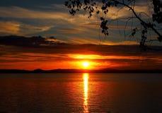 Verdunkelungssonnenunterganghimmel über dem See mit bunten Wolken, goldene Stunde stockbilder