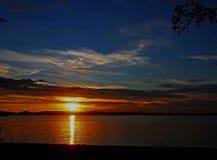 Verdunkelungssonnenunterganghimmel über dem See mit bunten Wolken, goldene Stunde lizenzfreie stockbilder