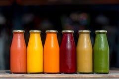 Verdura cruda y zumos de fruta en las botellas de cristal Fotografía de archivo libre de regalías