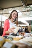 Verdura de compra de la mujer joven en parada en el mercado fotografía de archivo libre de regalías