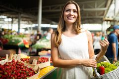 Verdura de compra de la mujer joven en parada en el mercado imagenes de archivo