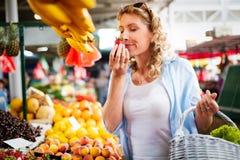 Verdura de compra de la mujer joven en parada en el mercado imagen de archivo libre de regalías