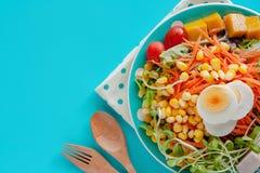 Verdura di insalata fresca con l'uovo bollito del pollo, il cucchiaio di legno e la forchetta su fondo blu immagine stock