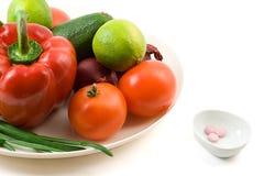 Verdura fresca contro la pillola di vitimin Immagini Stock