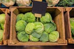 Verdura fresca de la col en parada de la caja de madera en verdulería con la etiqueta de la pizarra del precio Fotos de archivo