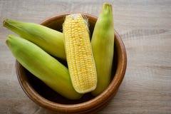 Verdura fresca del maíz en el cuenco de madera con el espacio y la madera de la copia imagen de archivo