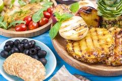 Verduras asadas a la parrilla, camarón, fruta en una placa de madera y las salchichas, jugo y ensalada en un fondo azul Cena del  Fotos de archivo libres de regalías
