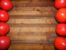 Verduras brillantes de los tomates rojos grandes a ambos lados de la tabla de cortar marrón ancha Fotos de archivo