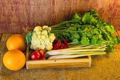 Verduras clasificadas en la caja de madera en de madera rústico oscuro y el saco s Imagen de archivo libre de regalías