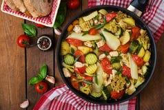 Verduras cocidas al vapor con el prendedero del pollo en cacerola en el fondo de madera Fotos de archivo libres de regalías