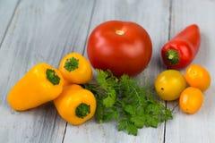 Verduras coloreadas frescas mezcladas, tomates de cereza, mini paprika, tomate e hierbas frescas en un fondo de madera Fotografía de archivo